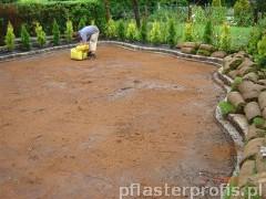 Pracownik przygotowujący teren pod trawnik z rolki